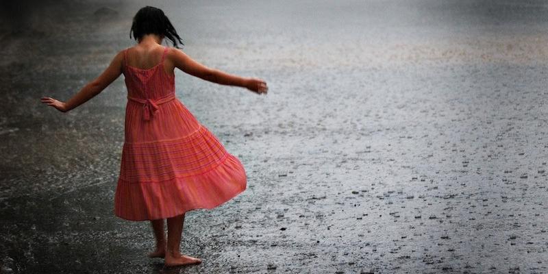 bambina cammina a piedi nudi sotto la pioggia