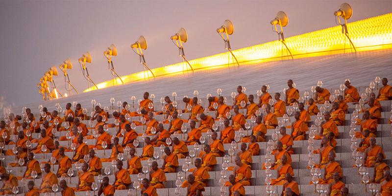 centinaia di monaci meditanti vestiti d'arancione sugli spalti di uno stadio