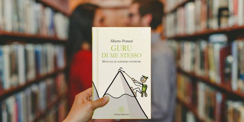 due ragazzi sullo sfondo in Libreria in primo piano Libro GURU DI ME STESSO Manuale di alpinismo interiore in primo piano su sfondo innamorati