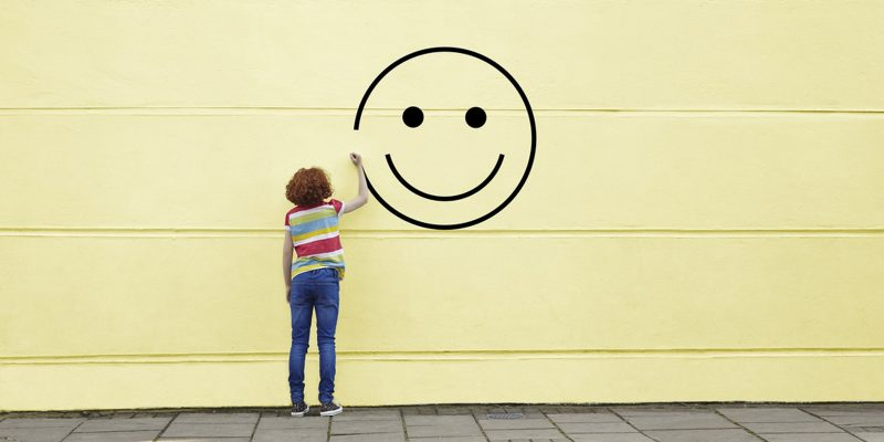 felicità-sorriso-disegnato-su-muro-da-ragazza-di spalle