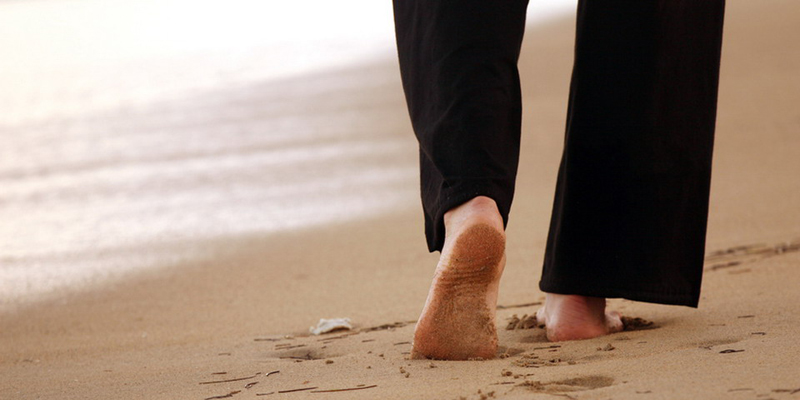 uomo che cammina a piedi nudi sulla sabbia